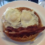 Waffle beneath egg and bacon happy face